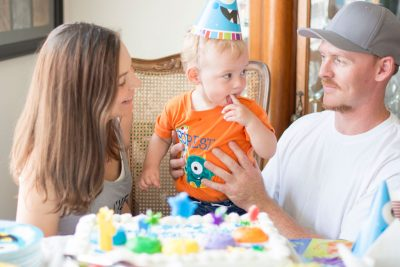 First birthday party photo with mom and dad before cutting the cake.
