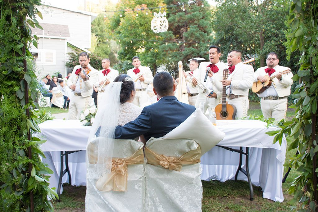 Bride and groom with mariachi band at wedding reception by Jackie Rutan Photography Oakland.